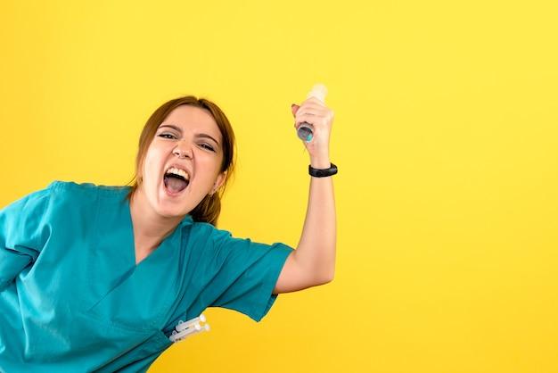 Widok z przodu kobiety lekarza weterynarii posiadającego ogromny zastrzyk na żółtej ścianie