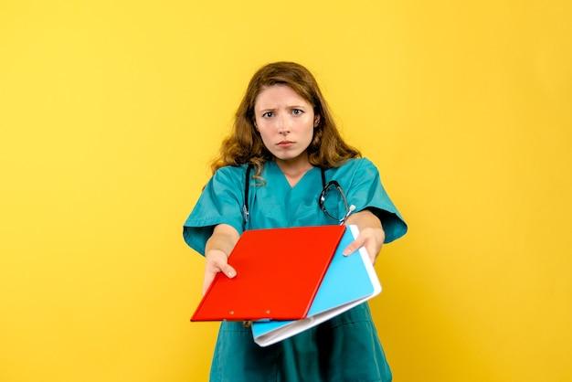 Widok z przodu kobiety lekarza z analizami na żółtej ścianie