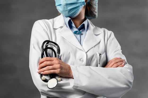 Widok z przodu kobiety lekarza z maską medyczną i siatka na włosy trzymając stetoskop