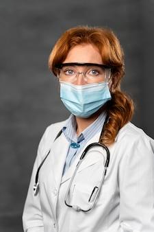 Widok z przodu kobiety lekarza z maską medyczną, stetoskopem i okularami ochronnymi