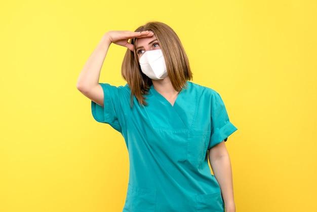 Widok z przodu kobiety lekarza z maską na żółtej ścianie