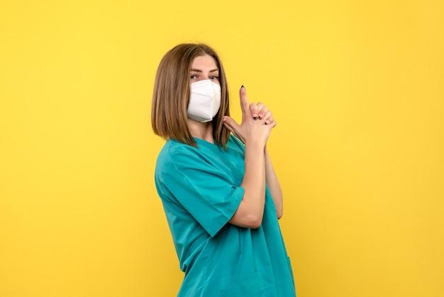 Widok z przodu kobiety lekarza z maską ochronną na żółtej ścianie