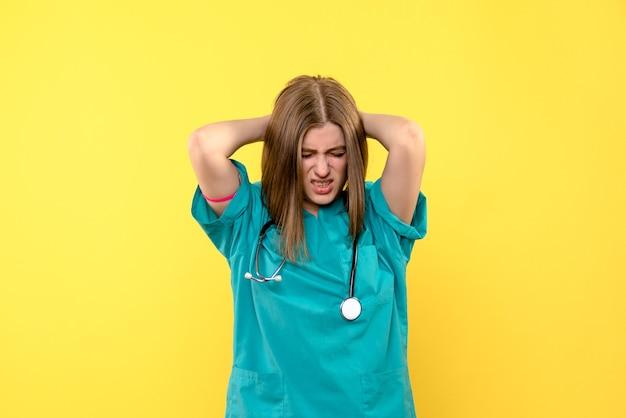 Widok z przodu kobiety lekarza z nerwowym wyrazem na żółtej ścianie