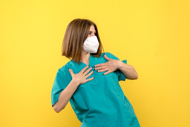 Widok z przodu kobiety lekarza z sterylną maską na żółtej ścianie