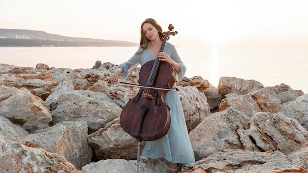 Widok z przodu kobiety muzyk grający na wiolonczeli na zewnątrz