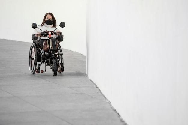 Widok z przodu kobiety na wózku inwalidzkim z maską i miejscem na kopię