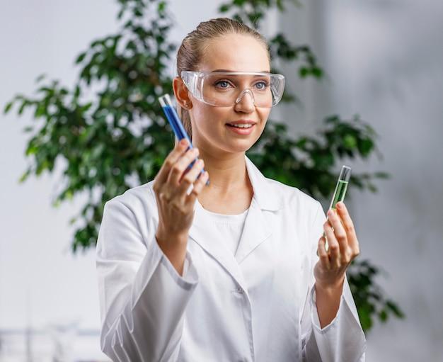 Widok z przodu kobiety naukowca z probówką i okularami ochronnymi