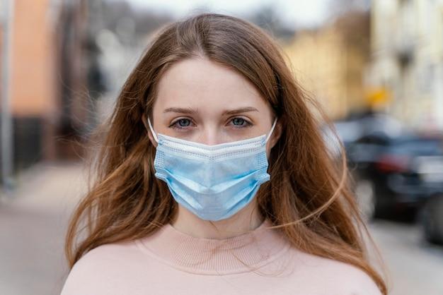 Widok z przodu kobiety noszącej maskę medyczną w mieście