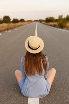 Widok z przodu kobiety pozującej na środku drogi w kapeluszu