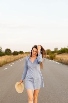 Widok z przodu kobiety pozuje na środku drogi z miejsca na kopię