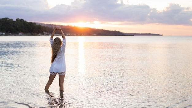 Widok z przodu kobiety pozuje na świeżym powietrzu w morzu