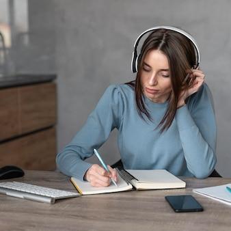 Widok z przodu kobiety pracującej w dziedzinie mediów ze słuchawkami