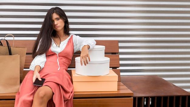 Widok z przodu kobiety siedzącej na ławce z pudełkami