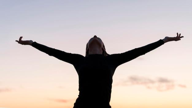 Widok z przodu kobiety stojącej z rękami do góry