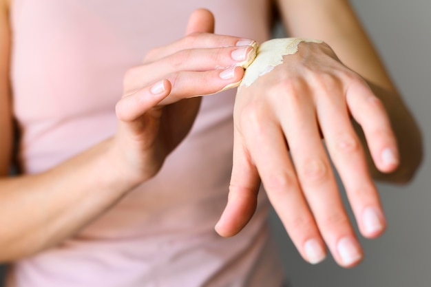 Widok z przodu kobiety stosowania balsamu na jej ręce