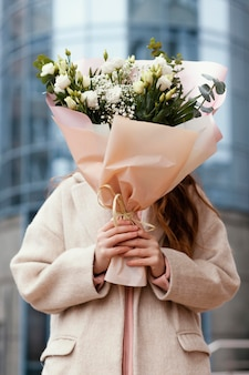 Widok z przodu kobiety trzymającej bukiet kwiatów przed jej twarzą na zewnątrz
