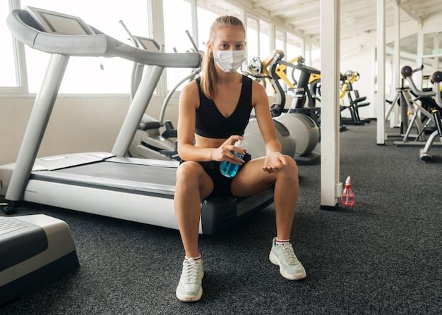 Widok z przodu kobiety używającej środka dezynfekującego do rąk podczas ćwiczeń na siłowni