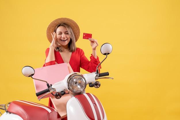 Widok z przodu kobiety w czerwonej sukience na motorowerze, trzymając torby na zakupy i karty