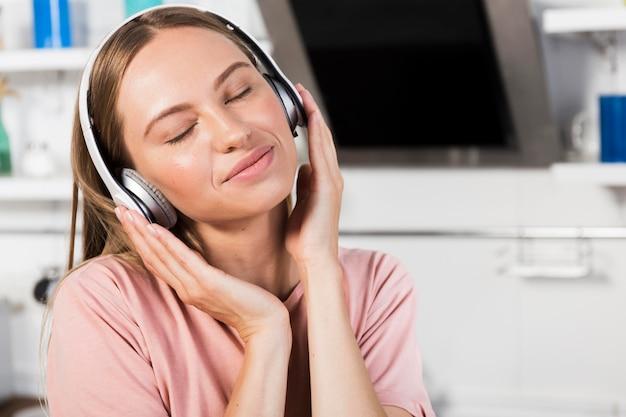 Widok z przodu kobiety w domu, słuchanie muzyki