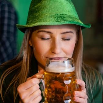 Widok z przodu kobiety w kapeluszu z okazji św. patrick's day z napojem