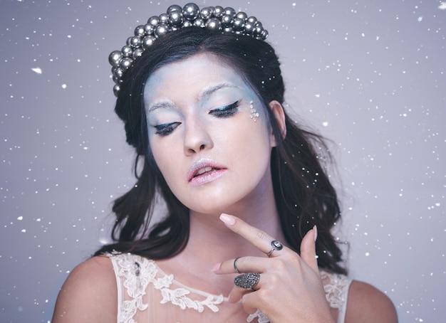 Widok z przodu kobiety w mroźnym makijażu wśród padającego śniegu