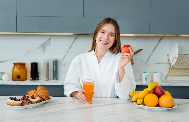Widok z przodu kobiety w szlafroku gospodarstwa jabłko