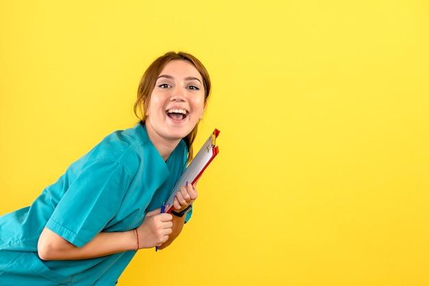 Widok z przodu kobiety weterynarza gospodarstwa analizy na żółtej ścianie