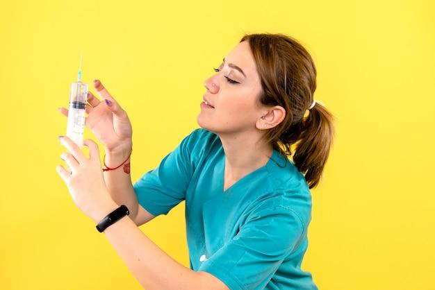Widok z przodu kobiety weterynarza gospodarstwa zastrzyk na żółtej ścianie