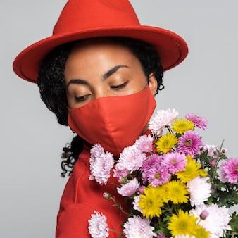 Widok z przodu kobiety z maską i kapeluszem
