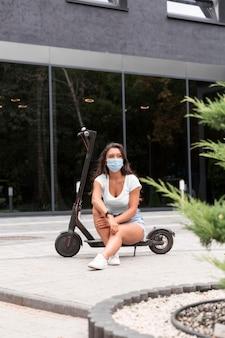 Widok z przodu kobiety z maską medyczną i skuterem na zewnątrz
