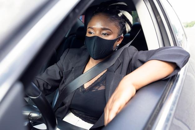 Widok z przodu kobiety z maską podczas jazdy samochodem