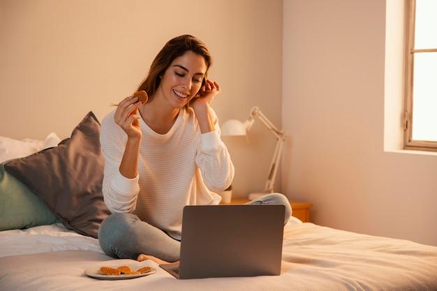 Widok Z Przodu Kobiety Za Pomocą Laptopa W Domu I Rozmawia Przez Telefon Darmowe Zdjęcia