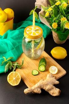 Widok z przodu koktajl cytrynowy świeży chłodny napój w szklanym kubku pokrojone w plasterki i całe cytryny ogórki wraz z kwiatami na ciemnym tle koktajl drink owoc