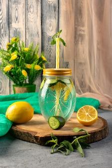 Widok z przodu koktajl cytrynowy świeży chłodny napój wewnątrz szklanego kubka pokrojone cytryny kwiaty słomka na drewnianym biurku i szare tło koktajl drink owoc