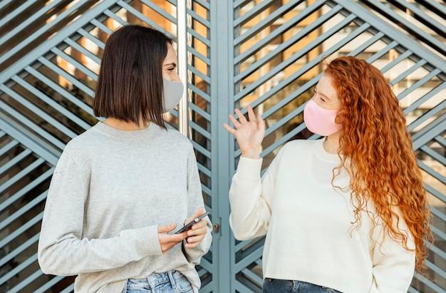 Widok z przodu koleżanek z maskami na twarz rozmawiających na zewnątrz