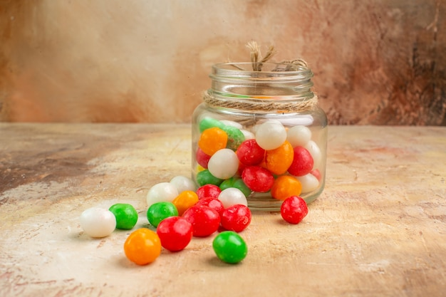 Widok z przodu kolorowe cukierki wewnątrz szklanej puszki na jasnym tle