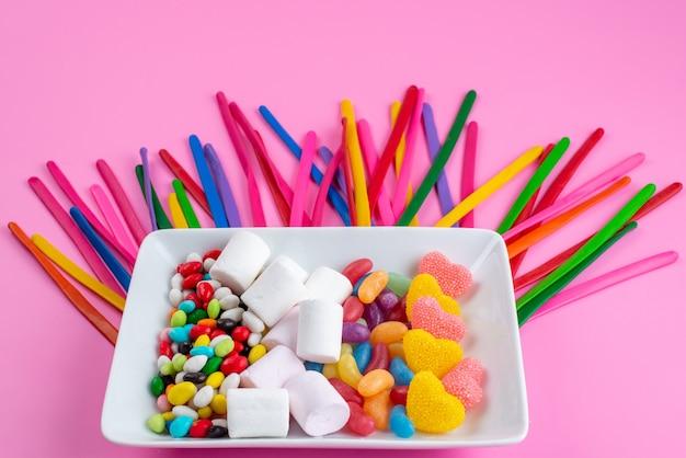 Widok z przodu kolorowe cukierki wraz z piankami i marmoladami na różowym, cukierkowym kolorze cukru