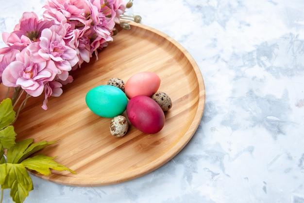Widok z przodu kolorowe pisanki na desce do krojenia na białym tle słodkie ciasto kolorowa koncepcja wielkanoc wiosna ozdobny