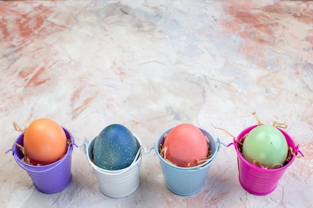 Widok z przodu kolorowe pisanki w osobnych małych koszyczkach na jasnym tle ozdobne wiosenne święta wielkanocne kolorowe poziome