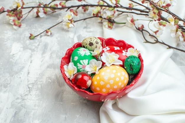 Widok z przodu kolorowe pisanki wewnątrz czerwonego talerza na białym tle novruz kolorowa koncepcja wielkanocna wiosna ozdobny