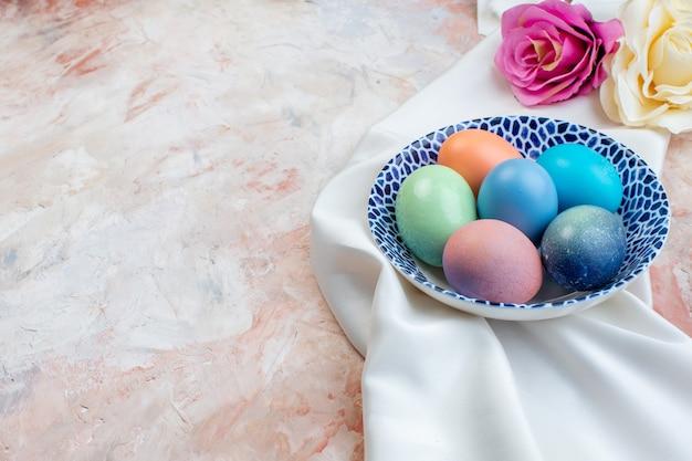 Widok z przodu kolorowe pisanki wewnątrz eleganckiej płyty na jasnym tle koncepcja poziome wielkanocne ozdobne kolorowe święta wiosna