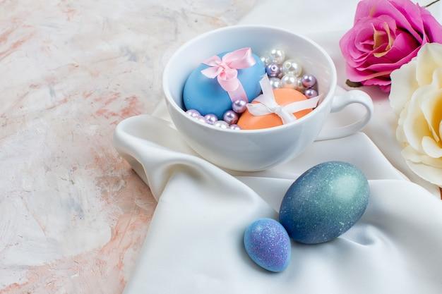 Widok z przodu kolorowe pisanki wewnątrz kubka z koralikami na jasnym tle poziome święta wielkanocne wiosna kolorowa koncepcja ozdobna