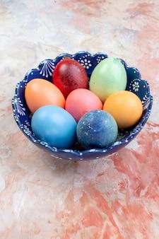 Widok z przodu kolorowe pisanki wewnątrz niebieskiego talerza na jasnym tle ozdobne wakacje pozioma kolorowa koncepcja wielkanoc