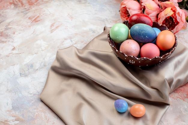 Widok z przodu kolorowe pisanki wewnątrz talerza na jasnym tle ozdobne wiosenne wielkanocne poziome wakacje kolorowe