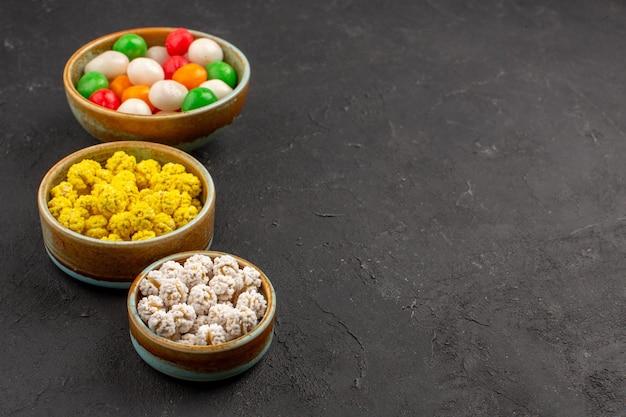 Widok z przodu kolorowe słodkie cukierki na ciemnej przestrzeni