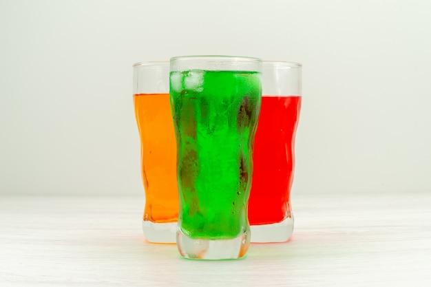 Widok z przodu kolorowe soki w długich szklankach na białej powierzchni