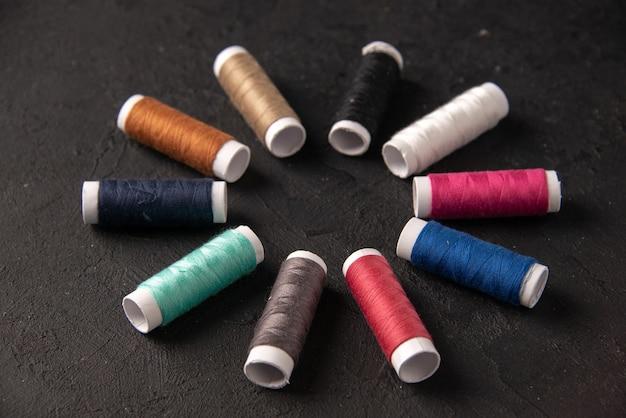 Widok z przodu kolorowych nici w kółku na ciemnej powierzchni