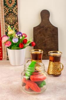 Widok z przodu kolorowych pysznych ciasteczek różnie uformowanych w środku puszki z kwiatami i filiżankami herbaty