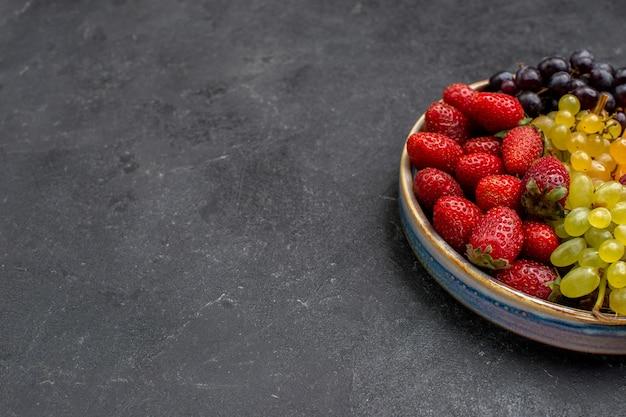 Widok z przodu kompozycja owocowa truskawki winogrona maliny i mandarynki na ciemnej przestrzeni