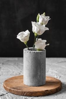 Widok z przodu kompozycji kwiatów w szarym wazonie
